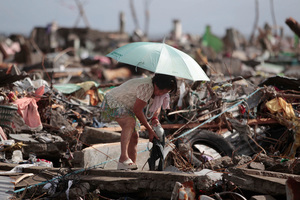A survivor salvages belongings from her damaged home. Photo / AP