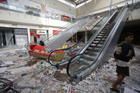 Filipinos walk inside a mall that has been flooded and allegedly looted. Photo / AP