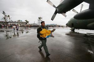 A trooper carries an elderly woman to a military plane. Photo / AP