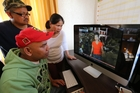 Yong Boquia, left, with Choi and Cres Marcial. Yong is pictured at his Whangarei home where his satellite television is feeding news live from the Philippines. Photo / John Stone