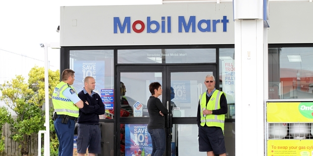 Police talk to staff outside the Mobil service station on Taradale Road, Napier, after an armed robbery yesterday morning. Photo / Duncan Brown