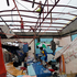 A resident walks inside a damaged home. Photo / AP