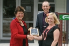 Councillor Shelley Deeming, whose children have attended Tauraroa Area School, presents principal Grant Burns and teacher Ellen Curnow with the School of Character award. Photo/Supplied.