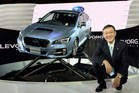 Fuji Heavy Industries President and CEO Yasuyuki Yoshinaga poses beside the company's new domestic sport touring wagon,