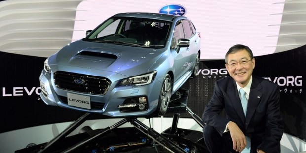 "Fuji Heavy Industries President and CEO Yasuyuki Yoshinaga poses beside the company's new domestic sport touring wagon, ""Subaru Levorg"" during a press briefing at the Tokyo Motor Show 2013 Photo / AFP"