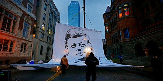 Crews raise a large banner on Main Street before the start of a ceremony to mark the 50th anniversary of the assassination of John F. Kennedy. Photo / AP