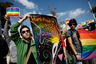 Gay activists hold rainbow flags and placards as they protest at the steps of the Acropolis' museum during an event last month. Photo / AP