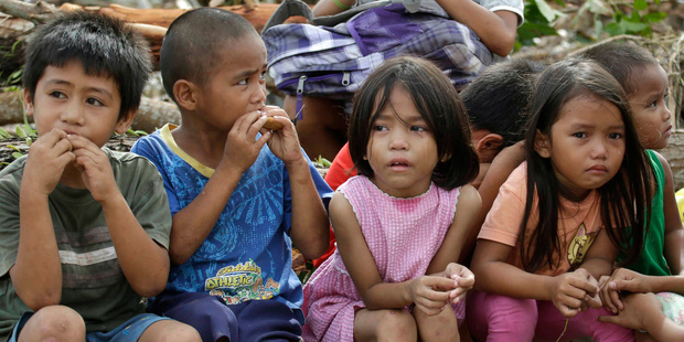 Children who say they fled when armed men were seen in their village eat bread while waiting in Tacloban city. Photo / AP