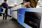 A man holds a Sony Playstation 4 after he purchased it in Chicago. Photo / AP