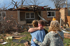 Ray Baughman embraces family shortly after his home was destroyed by a tornado that left a path of devastation through the north end of Pekin, Illinois. Photo / AP