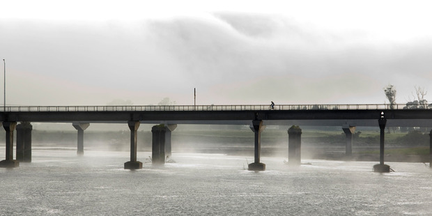 Mist rises from the Grey River as a cyclist rides across the Cobden Bridge in Greymouth. File photo / Mark Mitchell