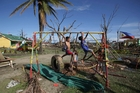 Children make use of the playground of the typhoon-damaged Pawing Elementary School in Palo town, Leyte province. Photo / AP