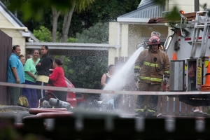 Firefighters douse hot spots at the Onehunga house after yesterday's fatal fire. Photo / Brett Phibbs