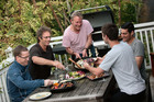 Grant Allen serves up food cooked on the barbecue to the 'boys left behind' ... Murray Hunt, Tony Reidy, Michael Reidy and Devin Deen. Photo / Chris Loufte