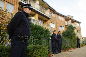 Police officers stand outside flats in the area where three women were rescued in south London. Photo / AP