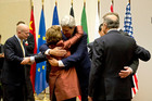 US Secretary of State John Kerry  (centre) embraces EU foreign policy chief Catherine Ashton in Geneva.  Photo / AP