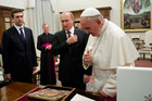 Russian President Vladimir Putin and Pope Francis cross themselves before an icon of the Madonna, given to the Pontiff by Putin. Photo / AP