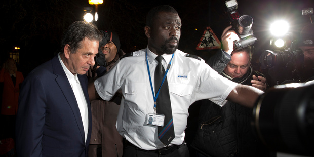 Art dealer Charles Saatchi, left, flanked by a security guard, leaves Isleworth Crown Court in London. Photo / AP