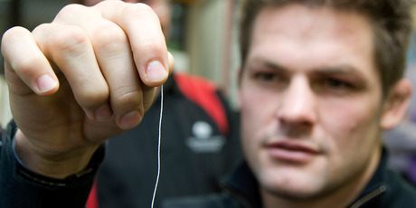 All Blacks captain Richie McCaw holds a thread imprinted with All Blacks names using Fibre Imprinting Nanotechnology.