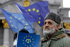 A demonstrator holds European Union flag during a protest in support of Ukraine's integration with the European Union in the center of of Kiev, Ukraine. Photo / AP