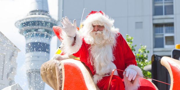 Santa waves to thousands of Aucklanders who gathered in the central city for Auckland's Farmer's Santa Parade. Photo: Greg Bowker