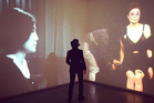 Yoko Ono stands between two screens showing her performing Cut Piece in 1965 and 2003 at the Museum of Contemporary art in Sydney.