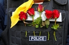 Roses offered by anti-government protesters decorate a Thai policeman's bulletproof vest yesterday. Previous clashes between police and protesters in Bangkok have left at least three people dead and more than 220 injured. Photo / AP