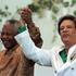 Libyan President Moammar Gadhafi, right, and Nelson Mandela salute the crowd as they arrive at the congress center in Zuwarah, Libya on October 29, 1997. File photo / AP