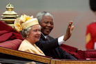 Nelson Mandela and Britain's Queen Elizabeth II ride in a carriage along the Mall, London, on the first full day of his state visit to Britain on July 9, 1996. File photo / AP