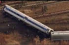 A New York City commuter train rounding a riverside curve derailed and came to rest only inches from the water, killing four people, injuring more than 60 and sending a chain of toppled cars shaped like a backward question mark trailing off the track.