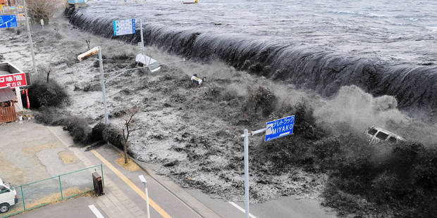 The tsunami gushes over the breakwater protecting the coastal city of Miyako.   Photo / AP