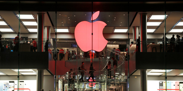 Shoppers visit the Apple store which changes its logo color to red in support for those living with HIV, in Hong Kong. Photo / AP