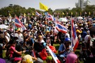 Anti-government protesters wave Thai national flags and yellow flags with an emblem of the Thai king as they listen to leaders speaking at Government House in Bangkok. Photo / AP