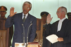Nelson Mandela, left, takes the oath of office in Pretoria, South Africa, to become the country's first black President. Photo / AP