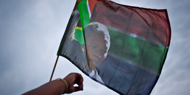 Mourners hold aloft a Nelson Mandela flag as they sing and dance to celebrate his life. Photo / AP