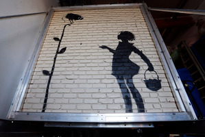 Banksy's 'Flower Girl,' a stencil on a massive brick wall, fetched more than $250K at auction. Photo / AP