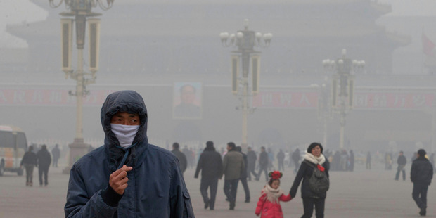 A man wears a mask on Tiananmen Square in thick haze in Beijing. Photo / AP