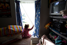 A 2-year-old girl looks out from the one room rental shared by her mother and father in Mangere. Photo / Richard Robinson
