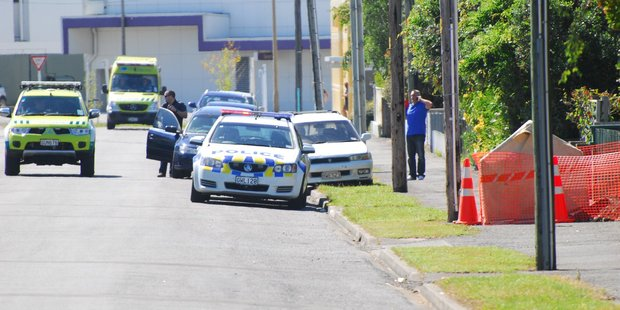 Paramedics and police make their way to a Cole St property in Masterton where a man died suddenly yesterday morning. PHOTO/NATHAN CROMBIE
