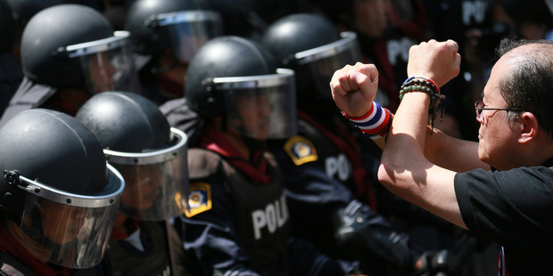 An anti-government protester crosses his arms in front of riot police as a gesture of his opposition to the government outside the headquarters of Prime Minister. Photo / AP