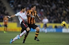 Hull City's Alex Bruce, right, and Liverpool's Luis Suarez tussle during Hull City's historic win. Photo / AP