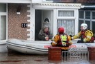 A woman and her dog are rescued by the RNLI or Royal National Lifeboat Institute in Rhyl, Wales. Photo / AP
