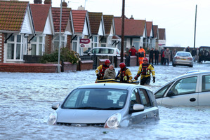 People are rescued by the RNLI from the floods as heavy seas and high tides sweep across the country, in Rhyl, Wales. Photo / AP