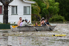 People in a boat negotiate flood water and debris in Bundaberg, Queensland. Photo / AAP
