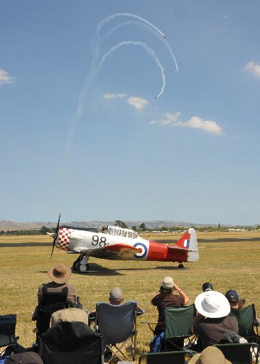 Wings Over Wairarapa Airshow, Hood Aerodrome Masterton, Saturday, a Harvard taxis past as the crowd is entertained by Yaks