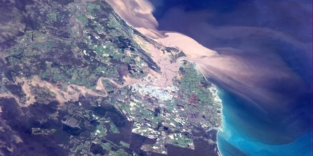 Floodwaters can be seen pouring into Bundaberg in this photo taken from the International Space Station. Photo / Commander Chris Hadfield/ISS