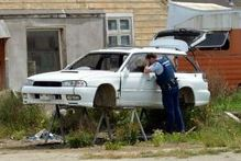 A police officer examines the shell of a stripped car at an alleged 'chop shop' on the outskirts of Mosgiel yesterday. Photo / Otago Daily Times