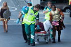 A casualty of the day is wheeled to an ambulance by paramedics and a colleague at the Hertz Sevens rugby tournament. Photo / Mark Mitchell