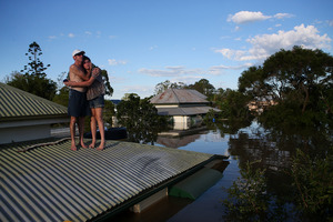 Flood victims in Bundaberg, north of Queensland, comfort each other after their property was inundated.  Photo / Getty Images