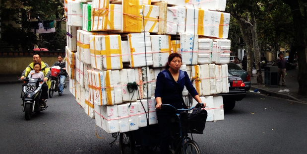 Commercial deliveries by bicycle pedallers are common sights in densely populated Shanghai. It may keep costs down but it looks to be an exhausting way to earn a living. Photo / Daniel Richardson